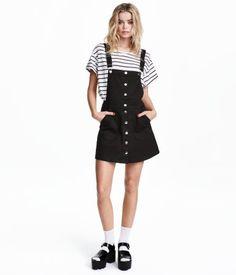 En kort kjol i stretchig bomullstwill. Kjolen har reglerbara hängslen. Knäppning och utanpåfickor fram.