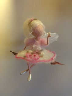 Little fairy sitting on a leaf with pearl. Very delicate pink and white dress with a pattern of flowers. Made from 100% merino wool felting technique. Some finishing details of white silk. It can be hung or placed on a plane. She holds on a palm natural pearl. Height of about 10-11 cm.