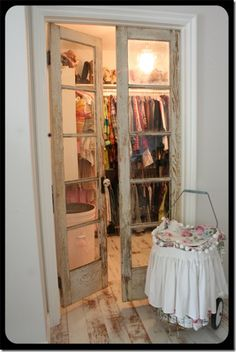 repurposed doors used as closet doors >> perfect for a smaller walk-in closet to make the room seem larger.