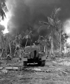 Supported by an M4A1 medium tank, infantrymen move forward on an island in the Kwajalein Atoll - February 1944