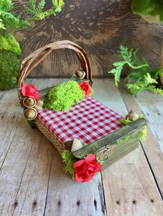 This petite fairy bed will add a touch of whimsy to your dollhouse or fairy cottage. The bed is made of wood which has been stained and distressed and the canopy is formed of bent twigs. Sweet red roses and red checked bedding add a touch of color. This bed is adorned with moss, acorns and jute trim. This fairy bed measures about 3 1/2 high, 3 wide and 4 deep. This fairy dream bed is for indoor display only.