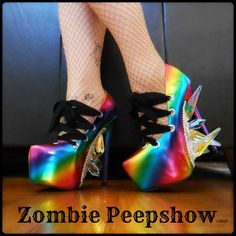 These ZombiePeepshow Over The Rainbow platform pumps are an addition to the Oz Collection. Each shoe features iridescent crystals, rainbow finish, and front lacing. They were hand painted and custom made for a client, so the final product you receive will have slight variances (ie, positioning and variation of crystals used, paint, etc.) so that no two pair of heels are the same. Extra care should be considered when wearing these with the glass spikes. They are extremely durable, but not…
