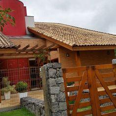 Fachada em tijolo cerâmico aparente, com muro em pera e telhado telha cerâmica, portão em madeira, jardim frontal. Cunha, São Paulo, Brazil.