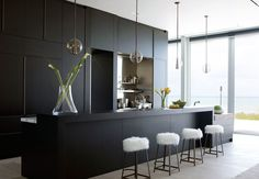 Hidden work surface .... though don't want chairs all the way along. Dark wenge cabinetry elegantly conceals prep and pantry space. A breakfast bar in a glossy white custom designed by DJDS can be hidden as well.