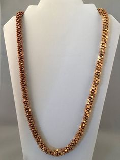 This Kumihimo necklace not only blends colors - it blends shapes. Starting with copper colored round seed beads it gradually mixes with gold colored cube seed beads. The transition is very subtle and unique and will surely be a conversation starter. This piece is finished off with an