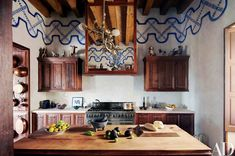 The kitchen cabinets are sabino and reclaimed pine, and the hood over the Viking range is fronted by a sabino-framed mirror.
