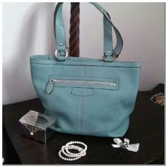 """Tiffany Blue Leather Coach Gorgeous tiffany blue pebbled leather Coach Penelope shoulder bag with silver hardware. Interior is flawless sateen with 2 slip pockets and a zip pocket. Exterior in great condition, featuring a huge rear slip pocket and front zip pocket. Bag measures 13""""x11""""x4"""" with 9"""" strap drop. Gorgeous color, hard to find. Zip top closure. Light patina on straps, pictured in 4th photo, minor. Very minor light scuff to 2 bottom corners, in 4th photo. In 8.5/10 condition…"""