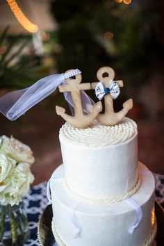 Nautical wedding cake idea - two-tiered, fondant-frosted cake with anchor topper and rope icing details {Carmen Ash Photography}