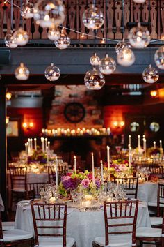 Adirondack wedding decor with handing candles and jeweled tone centerpieces,  linens, and chivari chairs at the Lake George Club in Lake George, NY