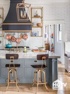 This kitchen is made glam with a powder-coated-wood range hood in black and gold, custom-color gray blue cabinets, luxe marble countertops and gold-toned shelves.
