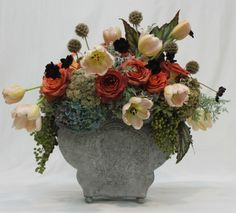 By Holly Bryan Floral & Botanical Design , Atlanta Coffee Break rose, Sedum, Dust Miller, Artemisia, Rex begonia leaves, Antique hydrangea, and Scabiosa pods, Chocolate cosmos, tulips, and Nandina berries.Flower Arranging 101: Yes YOU Can!