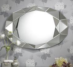 This larger Pyramid mirror has a sort of flattened oval shape made with straight edges. The geometric border is made up of triangular sections of clear glass forming pyramid type shapes, giving the border an interesting 3D multifacet effect.