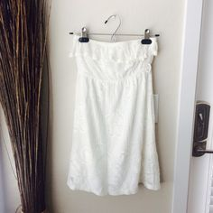 Strapless white dress White lace/mesh print strapless dress with lining. It has a belt loop right under your bust where it scrunches. You can wear it without the belt or cut the belt loop if it bothers you. Really cute for a spring/summer dress. Forever 21 Dresses