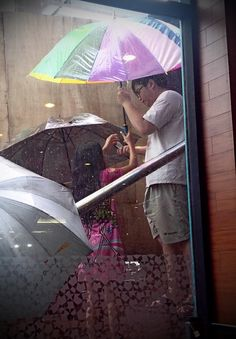 In the middle of the rain, a small girl rent her umbrella for 20 cents