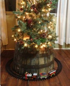 Train around a Christmas tree on top of a whiskey barrel.