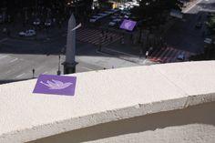 """Olhe para o céu (2009)  Praça Sete – Belo Horizonte, MG  Panfletos com imagens de pássaros foram arremessados do último andar de um dos prédios localizados no principal cruzamento da região central da cidade. Devido à massa de ar, esses """"pássaros"""" sobem ao invés de cair, o que provoca a ocupação momentânea e colorida do céu e desvia o olhar das pessoas para cima."""