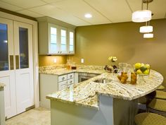 Shane Inman designed this basement kitchen featuring marble countertops with breakfast bar.