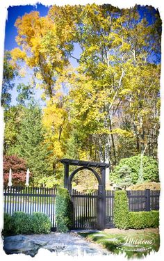 """V700-5L105. Grand Illusions Color Spectrum Black (L105) Classic Victorian 1.5"""" x 1.5"""" picket fence that is 5' high. Shown with a gorgeous VPER4P-4 4 Post Pergola w/ Inside Arch. Look at how the black accents the colors in the background. Illusions Vinyl Fence is the manufacturer of this amazing fence. #illusionsfence"""