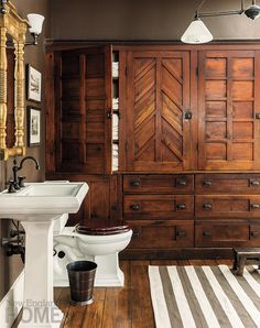 A beautiful cupboard originally found in this historic home's pantry provides ample linen storage in the bathroom.