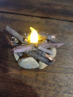 Flickering Fire Pit Miniature perfect for your fairy garden, gnome garden, or miniature garden! The fire pit features rocks around the perimeter and real wood by the faux flame. The fire pits flicke