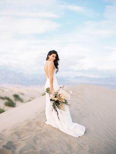 Boho bride wearing a flowy dress with low back for desert wedding