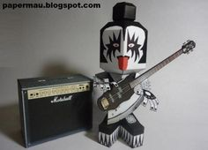 Kiss - Gene Simmons Paper Toy - by Papermau Download Now!  ==          This is the Gene Simmons Paper Toy, a free paper model create by a fan to be shared with all fans of Kiss. It is a nice collectible to put on your CD or old Lps shelf. The paper Gene Simmons measures 13 cm tall without the base and you can choose between a simple bass or a detailed bass to build.