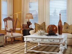 Inspired by French Provincial style, this living room contains an upholstered sofa, an ornate carved chair and a plaid area rug. The distressed wood coffee table is a distinct nod to French country design.