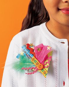 Using crepe paper, a feather, stars, and ribbon, kids can layer items on a triangle precut from card stock. Once they add a self-adhesive pin backing (available at crafts stores), they'll be ready for the fanciest of events.