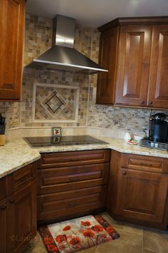 At the center of this kitchen renovation is the corner cooktop with a diagonal hood, and the tumbled marble mosaic backsplash coordinates with the solarus countertop.   The bi-level island includes a built-in double-single wall oven, and the lower island level seats three with ample space for food preparation and entertainment.  The cooktop is set in a 3-drawer cabinet with the bottom two drawers large enough to hold pots and pans.