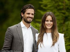 Prince Carl Philip and his wife Princess Sofia posed for waiting photographers after the rain had died down