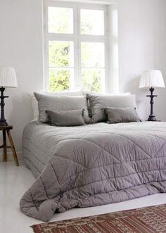 Vaalea makuuhuone, harmaa päiväpeitto.