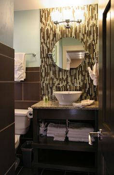 Vertically set glass tile, a round mirror and a vessel sink create a fun and inviting powder room.
