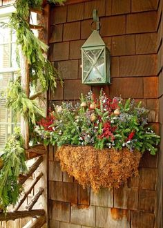 A wire wall container, lined with moss and filled with florist foam, showcases Fraser fir, burgundy-dyed eucalyptus, purple caspia, winterberry holly and poppy pods. More winter container garden ideas: http://www.midwestliving.com/garden/container/winter-container-gardens/?page=2,0