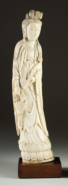 CHINESE CARVED IVORY FIGURE of a standing female holding a basket of fish in one hand and a scepter in the other. Height 12.25 inches (not including wood base).