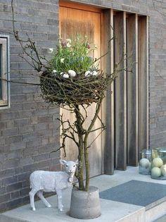 Osterdekoration für draußen: Osternest aus Kirschzweigen mit Frühlingsblumen