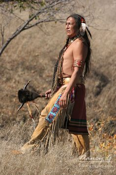 A Native American man standing with a weapon with horns. Nancy Greifenhagen Photography