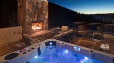 Outdoor seating area with jacuzzi and fireplace