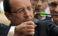 French President François Hollande tries archery at the French Olympic team's training camp at the National Institute for Sport and Physical Education HQ in Paris.
