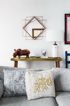 "The entryway table is one of Megan's favorite moments of the home, accessorized with a sculptural mirror and a simple but elegant <a href=""http://westelm.7eer.net/c/343160/277866/4336?aadid=112524&u=http%3A%2F%2Fwww.westelm.com%2Fproducts%2F112524%2F%3FcatalogId%3D71%26sku%3D112524"">lamp</a>."