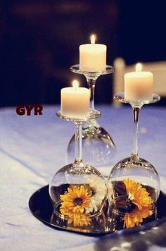 Wine Glasses Upside down with flowers inside and candle on top...