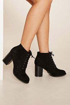 A pair of faux suede ankle booties with a lace-up top and a block heel.