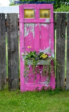 Repurpose old doors as backyard decor with paint & plastic planter boxes.