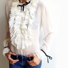 Anne Fontaine has created Victoria-era inspired chiffon blouse, adorned with multiple flounces at the front for a ruffle effect and at the cuffs. Blouse has a stand-up flounced collar with cuffs underlined by a black velvet drawstring. Long sleeve blouse in crinkle chiffon. Gathered flounces mid-front and at sleeve bottoms. Neck and cuff enhanced by a black velvet ribbon bow.