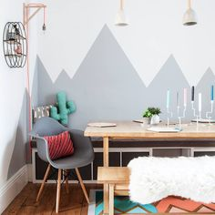Think different when painting a feature wall and paint pleasing shapes - like the wall of this dining nook painted in stylized, mountain forms. #diningrooms #diningroomideas #decorideas #paintideas