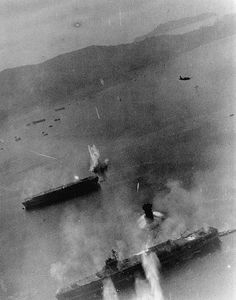 U.S. Navy planes from the aircraft carrier USS Essex (CV-9) attack two Japanese aircraft carriers at Kure, Japan, on 19 March 1945. A SB2C is visible in the upper rights. The ship at bottom is either Amagi or Katsuragi. The other carrier is Kaiyo.