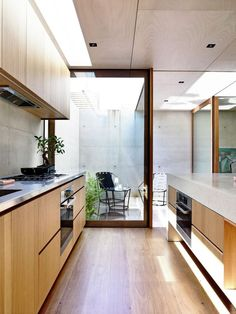 Light wood kitchen cabinetry with sliding door to small patio