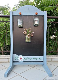 One side with lanterns, How to Give New Life to a Chalkboard Stand theboondocksblog.com