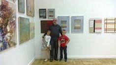 Yuri Yudaev with grandkids in front of five of his abstract works exhibited at the Central House of Artists, Moscow. September 2014.