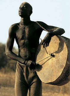 Dinka Man Playing Drum. Photo © Carol Beckwith Angela Fisher.