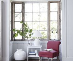 Beautiful farmhouse nook featuring rustic window frames, hardwood floors, white walls and a magenta chair | Neptune